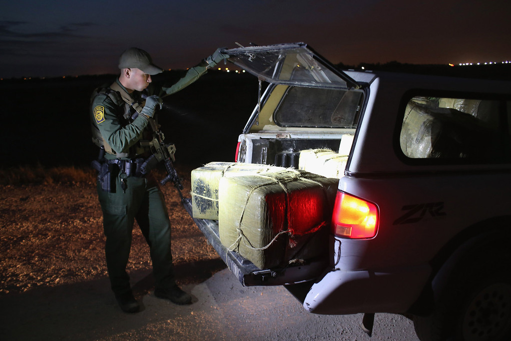 Description of . HIDALGO, TX - APRIL 10:  A U.S. Border Patrol Agent inspects a load of marijuana seized from drug smugglers near the U.S.-Mexico border on April 10, 2013 in Hidalgo, Texas. The agents, guided by helicopter surveillance from the U.S. Office of Air and Marine, waited more than four hours in hiding before seizing more than 900 pounds of the drug. The smugglers ran and escaped by swimming back across the Rio Grande River into Mexico. Border Patrol agents say they have also seen an additional surge in immigrant traffic since immigration reform negotiations began this year in Washington D.C. Proposed refoms could provide a path to citizenship for many of the estimated 11 million undocumented workers living in the United States.  (Photo by John Moore/Getty Images)