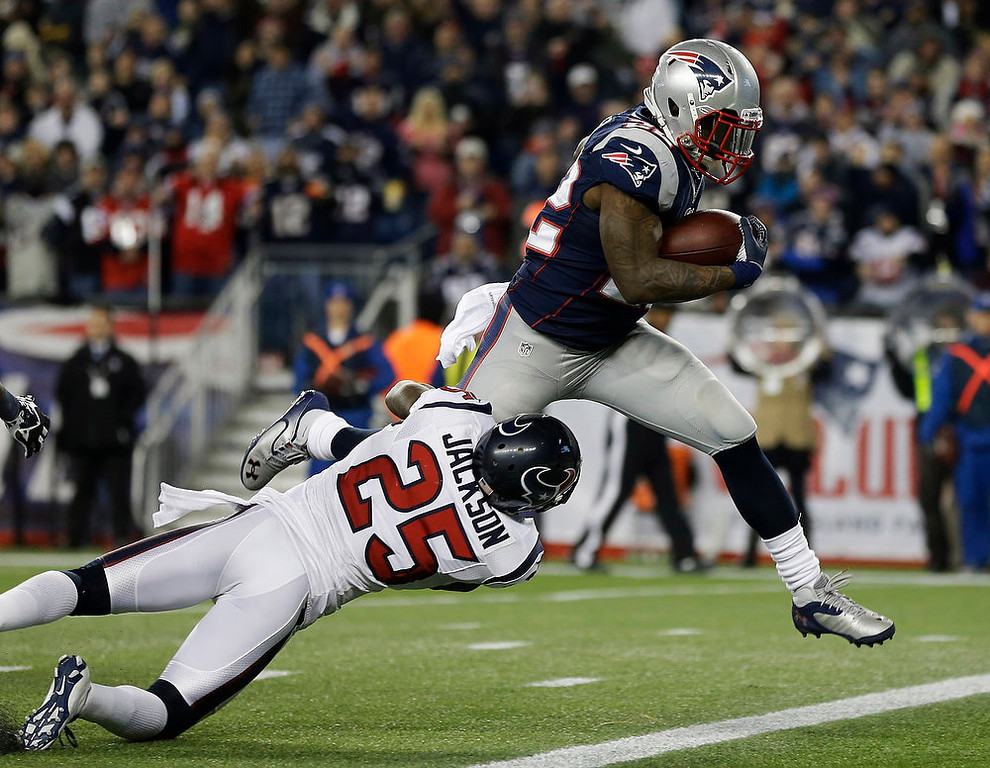 Description of . Houston Texans cornerback Kareem Jackson (25) cannot restrain New England Patriots running back Stevan Ridley as he crosses the goal line for an eight-yard touchdown during the second half of an AFC divisional playoff NFL football game in Foxborough, Mass., Sunday, Jan. 13, 2013. (AP Photo/Elise Amendola)