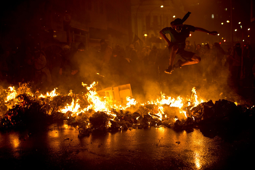 Description of . A demonstrator with his face covered jumps over a burning barricade at the Cinelandia square during a march in support of teachers on strike in Rio de Janeiro, Brazil, Monday, Oct. 7, 2013. (AP Photo/Felipe Dana)