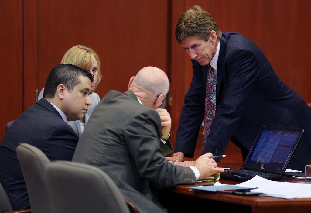 Description of . George Zimmerman, left,  confers with his defense counsel, Mark O'Mara, Don West, and Lorna Truett, background, after working out the wording of instructions for a possible charge of manslaughter, on the 25th day of Zimmerman's  trial at the Seminole County Criminal Justice Center, in Sanford, Fla., Saturday, July  13, 2013. Zimmerman has been charged with the 2012 shooting death of Trayvon Martin.(AP Photo/Orlando Sentinel, Joe Burbank, Pool)