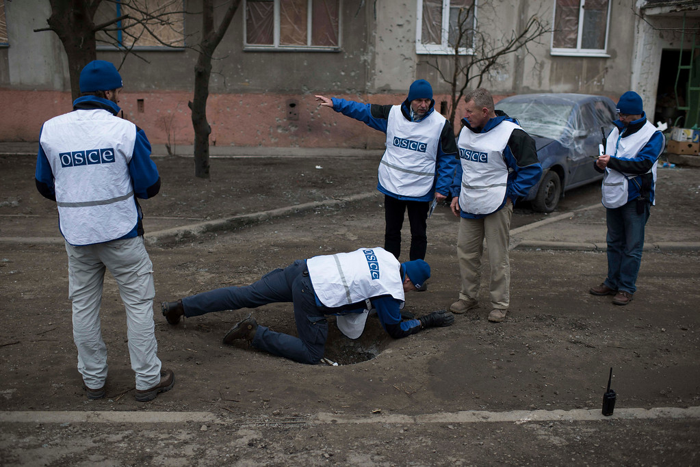 Description of . Organization for Security and Co-operation in Europe (OSCE) monitors investigate outside an apartment block damaged in Saturday's shelling in which scores of people were killed and injured in Mariupol, Ukraine, Tuesday, Jan. 27, 2015. European Union leaders are threatening fresh sanctions against Russia because of what it sees as