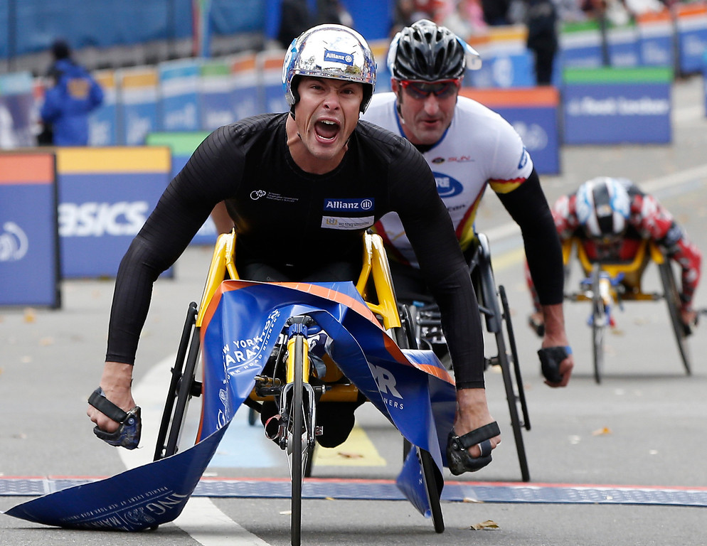 Description of . Marcel Hug of Switzerland reacts crossing the finish line followed by Ernst Van Dyk of South Africa, center, as he wins the mens' wheelchair division of the New York City Marathon, Sunday, Nov. 3, 2013, in New York. Person at rear right is unidentified (AP Photo/Kathy Willens)