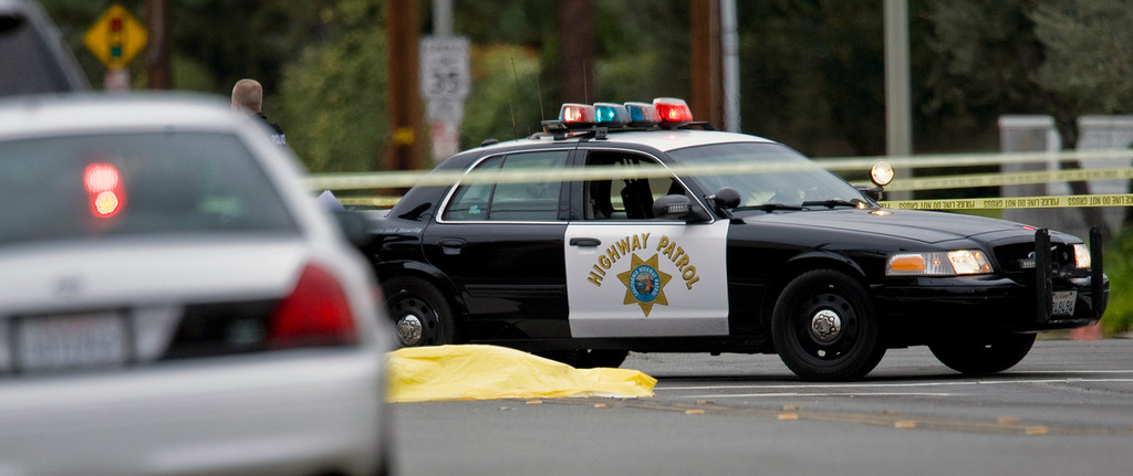 . A body lays in the intersection of Wanda Road and Katella Avenue early Tuesday, Feb. 19, 2013 in Orange County, Calif.,  as local police agencies investigate the scene.  (AP Photo/The Orange County Register, Mark Rightmire)