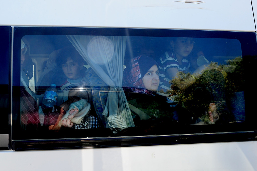 Description of . Syrian refugees leave on a bus on June 8, 2011 the Yayladagi Turkish Red Crescent camp near the Turkish city of Hatay. Turkey will not close its doors to hundreds of refugees fleeing repression in Syria, Prime Minister Recep Tayyip Erdogan said on June 8, voicing concern at growing unrest across the border. Some 120 Syrian refugees crossed over into Turkey late on June 7. Another 160 followed on June 8, bringing to at least 550 the number to enter the country in recent days. MUSTAFA OZER/AFP/Getty Images