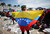 A woman holds a Venezuelan flag as people watch a live broadcast of the funeral for Venezuelan President Hugo Chavez outside the Military Academy on March 8, 2013 in Caracas, Venezuela.  (Photo by Mario Tama/Getty Images)