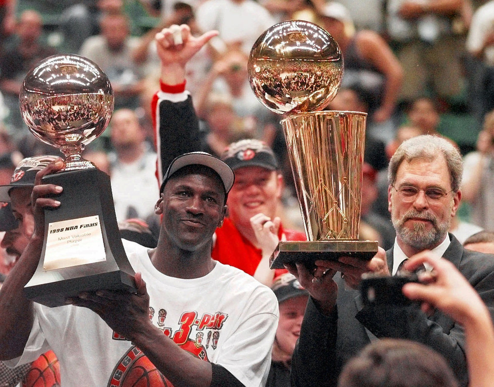 Description of . Chicago Bulls' Michael Jordan, left, holds the Most Valuable Player trophy as coach Phil Jackson holds the NBA Championship trophy after the Bulls defeated the Utah Jazz 87-86 in Game 6 of the NBA Finals in Salt Lake City, June 14, 1998.Jordan, regarded as the greatest player and greatest draw in NBA history, will announce his retirement from the Chicago Bulls on Wednesday, Jan. 13, 1999, The Associated Press has learned. (AP Photo/Jack Smith)