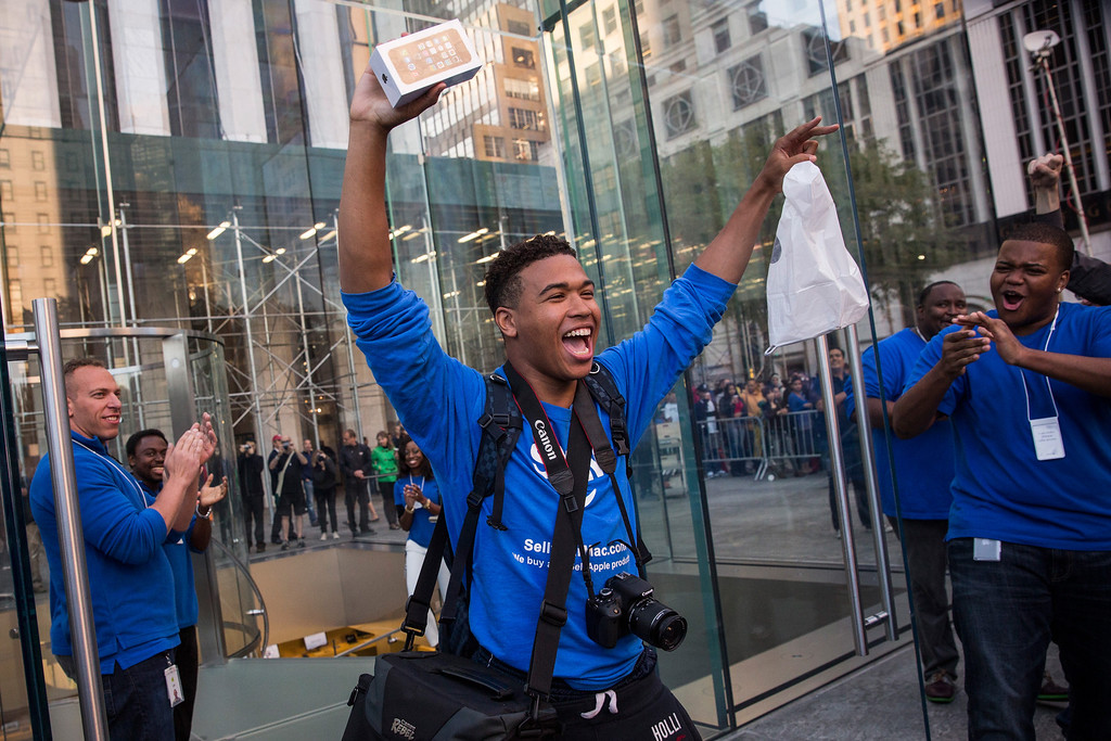 Description of . Brian Ceballo, who waited outside the Fifth Avenue Apple store for two weeks, walks out of the store after being the first person to buy an iPhone 5S on September 20, 2013 in New York City. Apple launched two new models of iPhone: the iPhone 5S, which is preceded by the iPhone 5, and a cheaper, paired down version, the iPhone 5C. The phones come with a new operating system. (Photo by Andrew Burton/Getty Images)