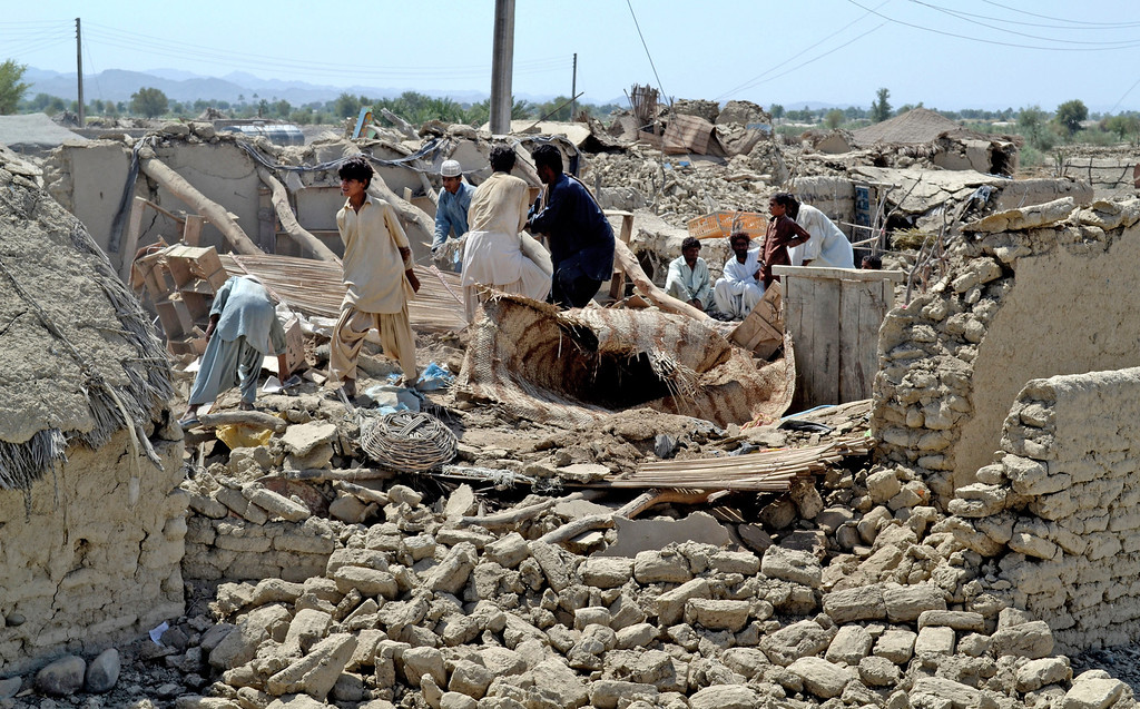 Description of . Pakistani villagers look for belongings amid the rubble of their destroyed homes following an earthquake in the remote district of Awaran, Baluchistan province, Pakistan, Wednesday, Sept. 25, 2013. Rescuers struggled Wednesday to help thousands of people injured and left homeless after their houses collapsed in a massive earthquake in southwestern Pakistan Tuesday, Sept. 24, 2013, as the death toll rose to hundreds. (AP Photo/Arshad Butt)