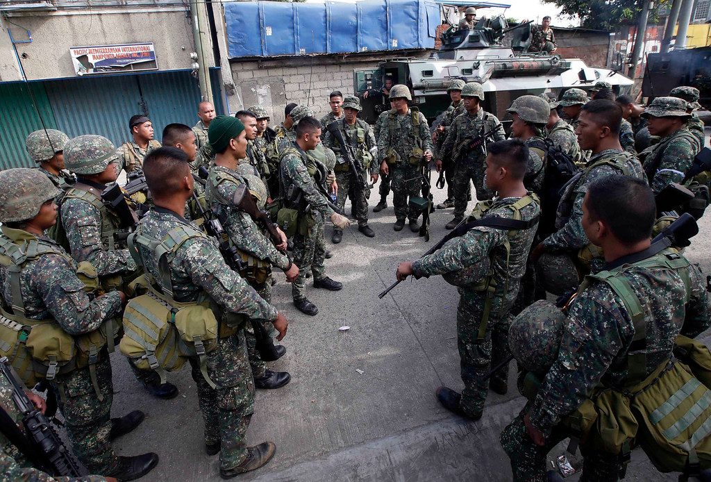 Description of . Government troopers gather for a last-minute instruction before heading out to rescue scores of hostages being used as human shields by Muslim rebels on the fourth straight day Thursday, Sept. 12, 2013 at Zamboanga city in southern Philippines. (AP Photo/Bullit Marquez)
