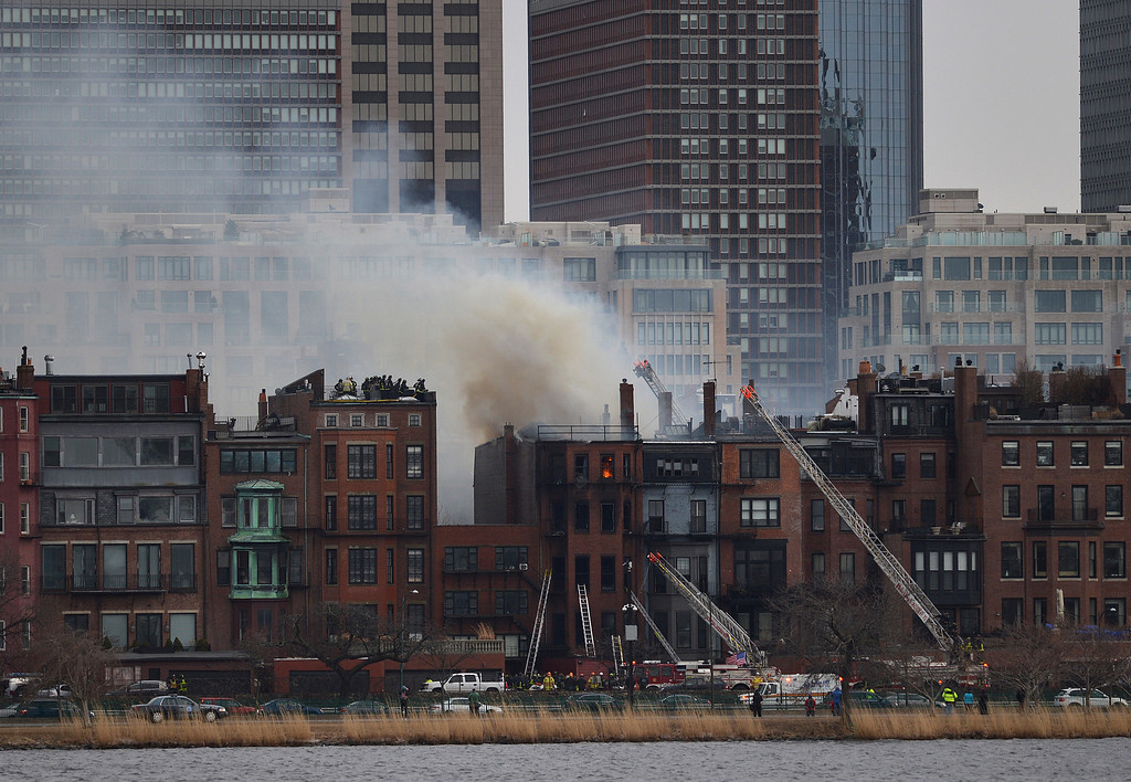 Description of . A multi-alarm blaze at a structure is seen from Cambridge, Mass., as firefighters respond, Wednesday, March 26, 2014. (AP Photo/The Boston Globe, Essdras M Suarez)