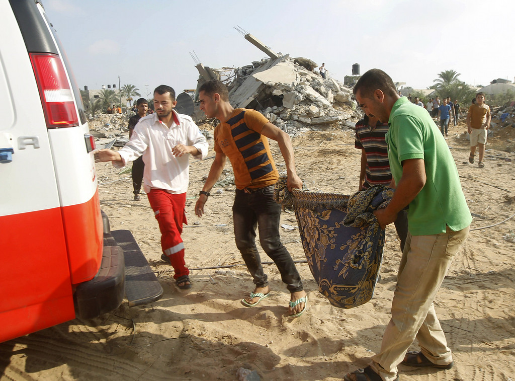 Description of . Palestinian rescue workers carry the body of a member of Duheir family, after removing it from under the rubble of a building destroyed by an Israeli air strike in Rafah on July 29, 2014, in the southern of Gaza strip. Bloodshed in war-torn Gaza surged with dozens more Palestinians killed as the conflict raged into a fourth week and Iran accused Israel of genocide in the tiny enclave.  AFP PHOTO/ SAID  KHATIB/AFP/Getty Images