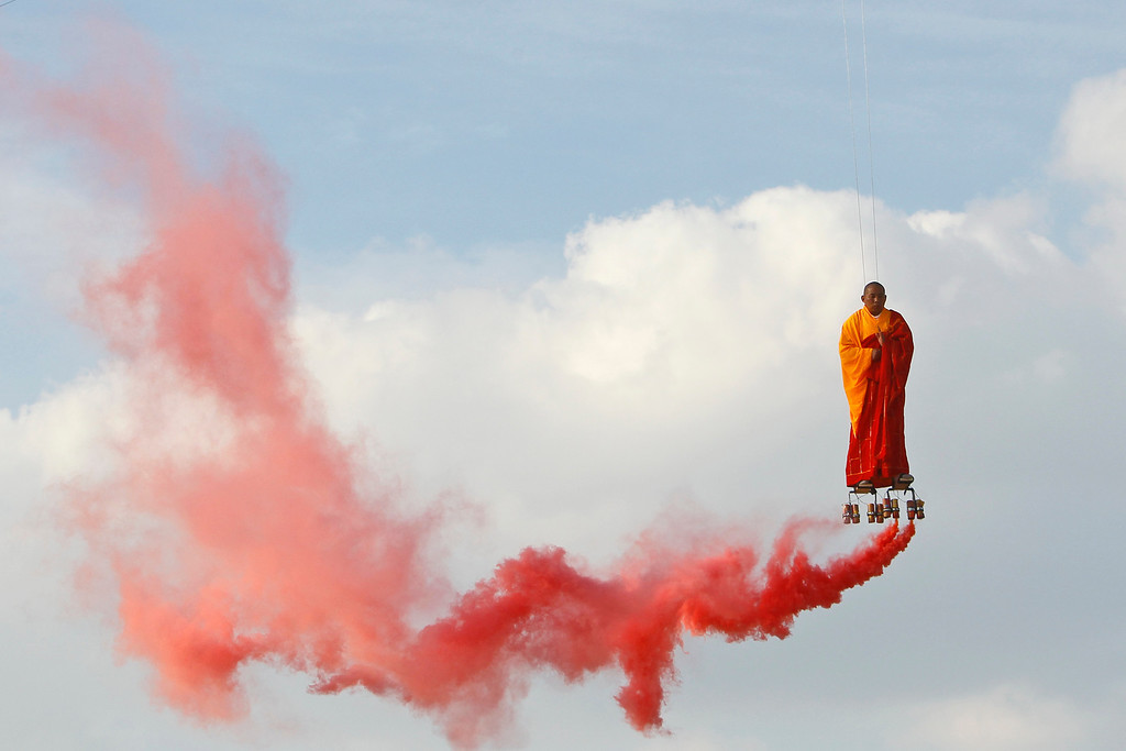 Description of . In this March 20, 2012 file photo, suspended by wires, Chinese artist Li Wei performs in the sky  at La Villette in Paris. Wei's work often depicts him in apparently gravity-defying situations. (AP Photo/Francois Mori, File)