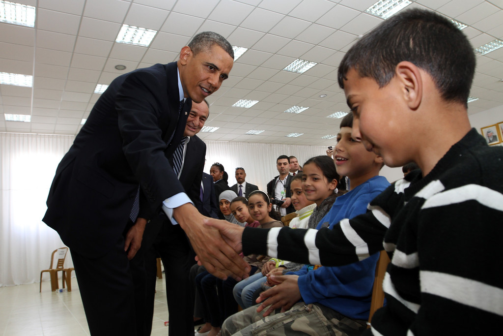 Description of . U.S. President Barack Obama shakes hands with Palestinian children during his visit to Al Bera Youth Center March 21, 2013 in Ramallah, the West Bank. (Photo by Alaa Badarneh-Pool/Getty Images)