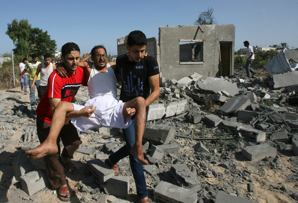 Description of . Palestinians help a man wounded as they walk over the rubble of destroyed buildings following an Israeli airstrike in Khan Younis in the southern Gaza Strip, Wednesday, July 30, 2014.(AP Photo/Eyad Baba)
