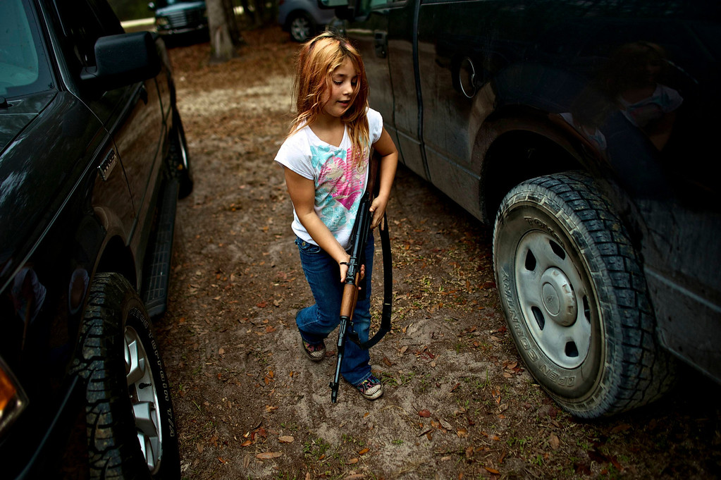 ". Brianna, 9, of the North Florida Survival Group carries an AK-47 rifle from the group leader\'s truck before heading out to conduct enemy contact drills during a field training exercise in Old Town, Florida, December 8, 2012.  The group trains children and adults alike to handle weapons and survive in the wild. The group passionately supports the right of U.S. citizens to bear arms and its website states that it aims to teach ""patriots to survive in order to protect and defend our Constitution against all enemy threats\"". Picture taken December 8, 2013.   REUTERS/Brian Blanco"