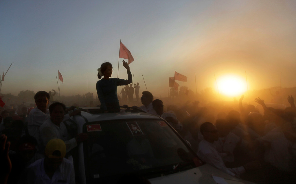 Description of . In this Feb. 26, 2012 file photo, Myanmar's pro-democracy icon Aung San Suu Kyi is silhouetted against setting sun as she arrived to deliver her speech during an election campaign rally in Thongwa village some 50 kilometers (31 miles) from Yangon, Myanmar. (AP Photo/Altaf Qadri, File)