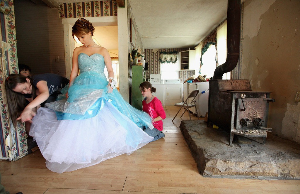 . Brittany Brewer (C) fixes her gown as she prepares for the Owsley County High School prom next to a wood stove in the home where she lives with her grandmother on April 21, 2012 in Booneville, Kentucky. Daniel Boone once camped in the Appalachian mountain hamlet of Owsley County which remains mostly populated by descendants of settlers to this day. The 2010 U.S. Census listed Owsley County as having the lowest median household income in the country outside of Puerto Rico, with 41.5% of residents living below the poverty line.  Familial and community bonds run deep, with a populace that shares a collective historical and cultural legacy uncommon in most parts of the country. However, the community of around 5,000 struggles with a lack of jobs due to the decline in coal, tobacco and lumber industries along with health issues including drug addiction without effective treatment.    (Photo by Mario Tama/Getty Images)