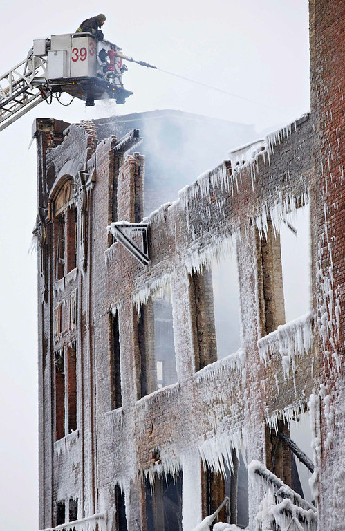 Description of . Firefighters spray down hot spots on an ice covered warehouse that caught fire Tuesday night in Chicago January 23, 2013. Fire department officials said it is the biggest fire the department has had to battle in years and one-third of all Chicago firefighters were on the scene at one point or another trying to put out the flames. An Arctic blast continues to gripped the U.S. Midwest and Northeast Wednesday, with at least three deaths linked to the frigid weather, and fierce winds made some locations feel as cold as 50 degrees below zero Fahrenheit. (minus 46 degrees Celsius) REUTERS/John Gress