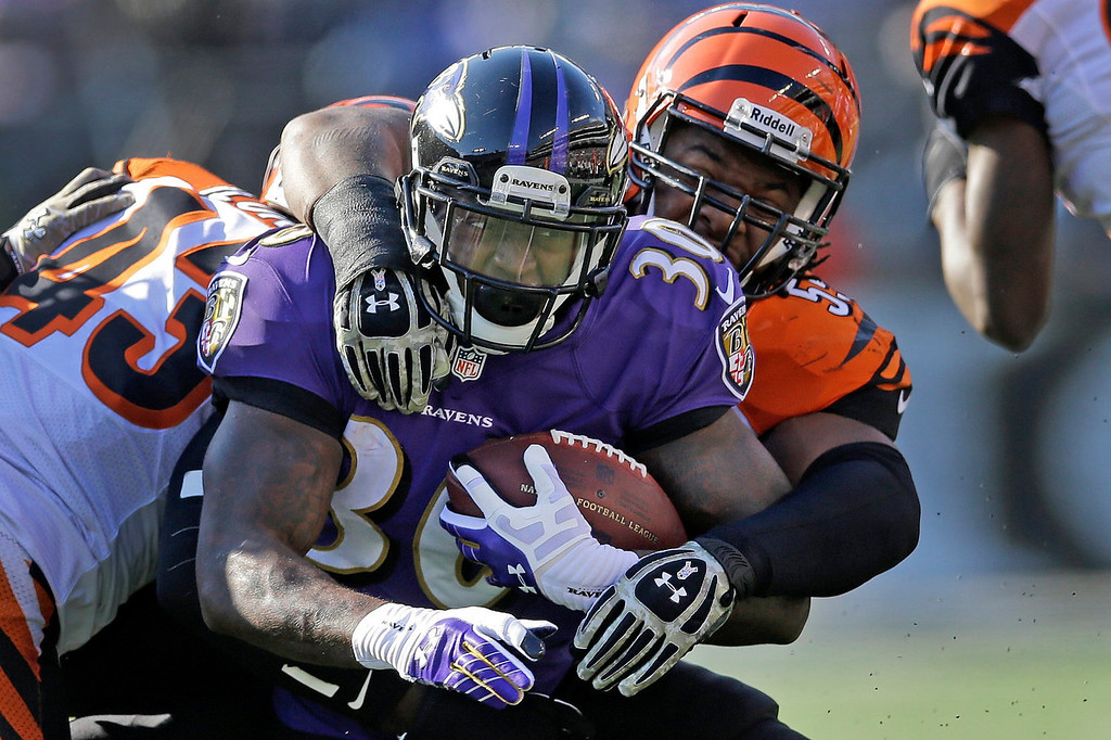 Description of . Baltimore Ravens running back Bernard Pierce is wrapped up by Cincinnati Bengals outside linebacker Vontaze Burfict, right, during the first half of a NFL football game in Baltimore, Sunday, Nov. 10, 2013. (AP Photo/Patrick Semansky)