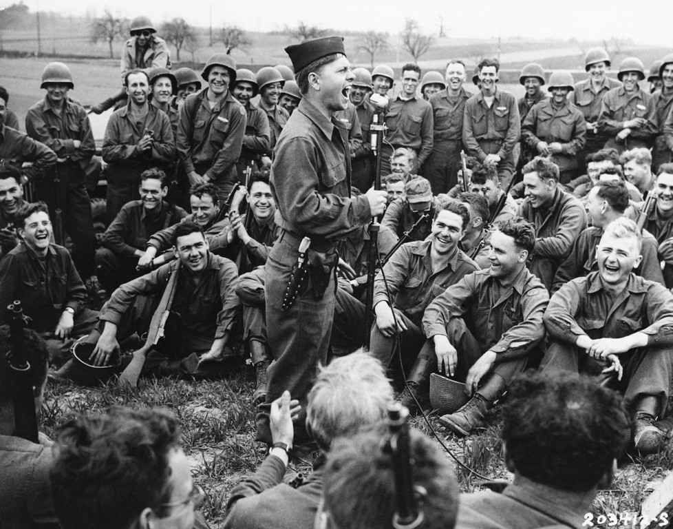 Description of . Pfc. Mickey Rooney, former film star, imitates some Hollywood actors for the entertainment of infantrymen of the 44th Division of the U.S. Seventh Army, April 24, 1945. Rooney is a member of a three-man unit making a jeep tour to entertain troops in Germany. (AP Photo)
