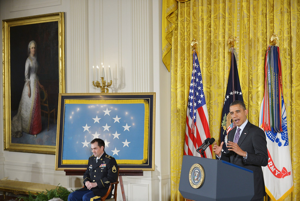 Description of . US President Barack Obama speaks before presenting  Clinton Romesha (L), former active duty Army staff sergeant, with the Medal of Honor during a ceremony in the East Room of the White House on February 11, 2013 in Washington, DC.  AFP PHOTO/Mandel NGAN/AFP/Getty Images