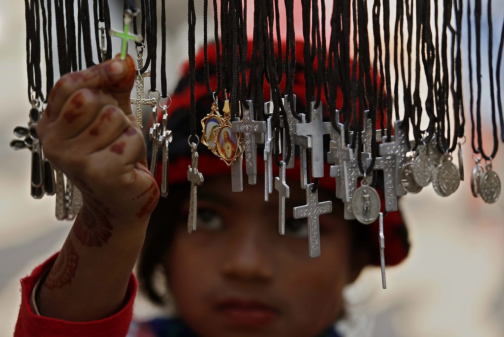 Description of . A Pakistani Christian girl buys crosses during Christmas celebrations, in Peshawar, Pakistan, 25 December 2013. Christians in Pakistan form the largest minority community, with about 1,6 per cent of the population. December 25th is celebrated as birth anniversary of Lord Jesus Christ. Christmas is basically celebrated by the Christians but it is also observed as a day of celebration by other communities around the globe.  EPA/ARSHAD ARBAB