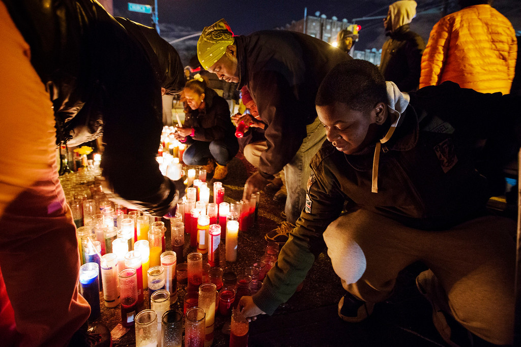Description of . Mourners light candles at a memorial for 16-year-old Kimani