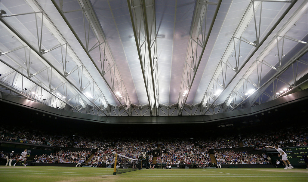 Description of . Andy Murray of Britain, right, serves to Jerzy Janowicz of Poland, left, during their Men\'s singles semifinal match at the All England Lawn Tennis Championships in Wimbledon, London, Friday, July 5, 2013. (AP Photo/Alastair Grant)