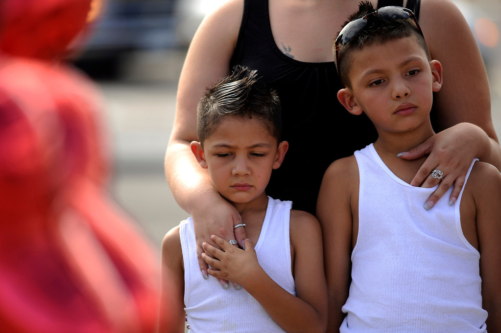 Description of . Jasmine Herrera of Denver, center, visits memorial for shooting victims with her sons Julio Garcia, 5, and Jeremiah Perez, 6, at the corner of E. Centerpoint Dr. and S. Sable Blvd. in Aurora, CO. Saturday, July 21, 2012.  Hyoung Chang, The Denver Post
