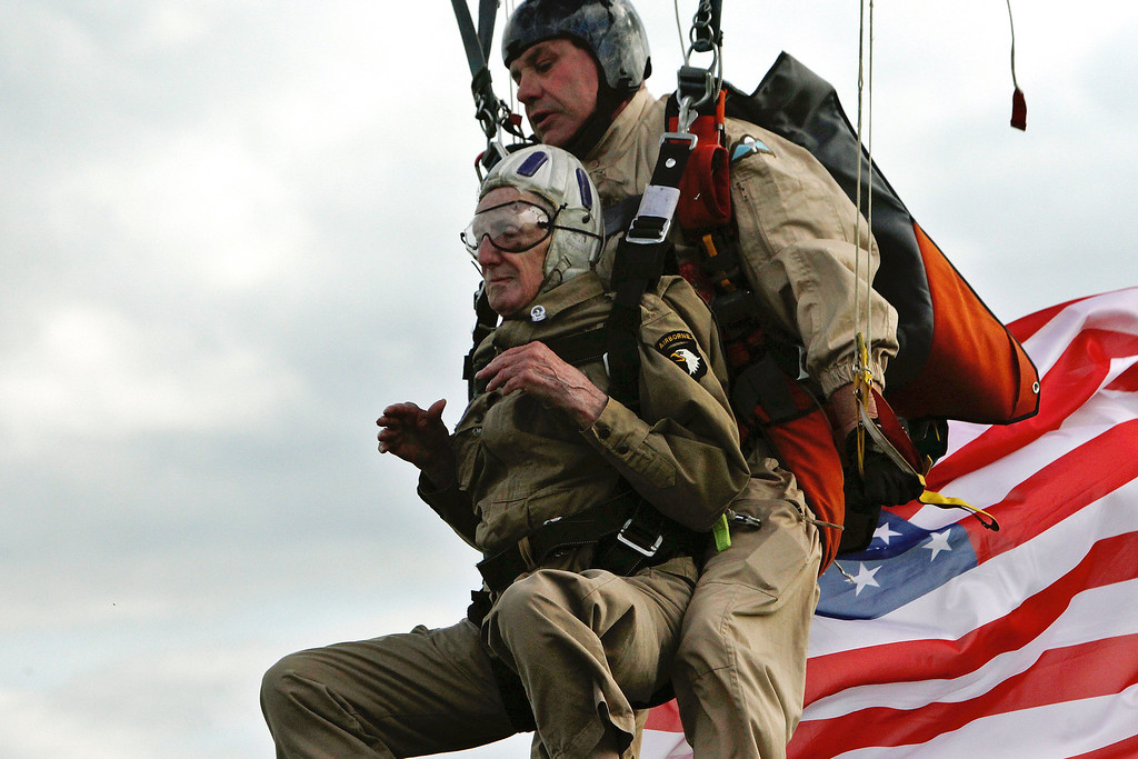Description of . 93 year old U.S WW II veteran Jim Martin of the 101st Airborne, left, completes a tandem parachute jump onto Utah Beach, western France, Thursday June 5, 2014, as part of the commemoration of the 70th anniversary of the D Day. World leaders and veterans prepare to mark the 70th anniversary of the invasion this week in Normandy. (AP Photo/Thibault Camus)