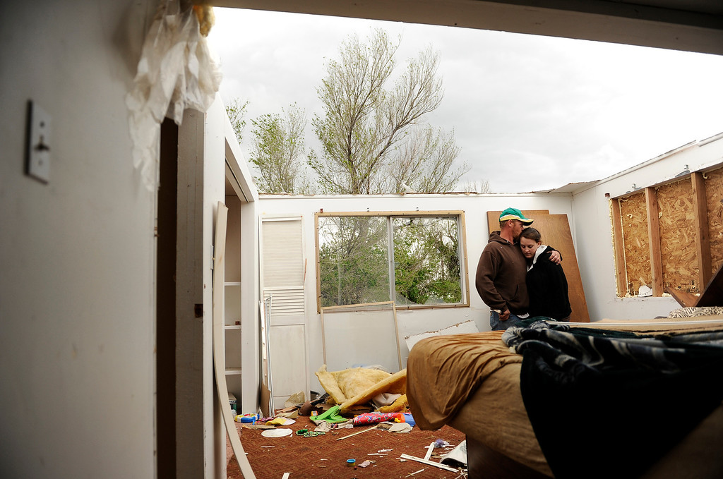 Description of . Josh Brown hugs his wife Therisa Brown, Friday April, 27, 2012, in their bed room where they were sleeping when a tornado went through their small town, Chivington, Co., last night. RJ Sangosti, The Denver Post