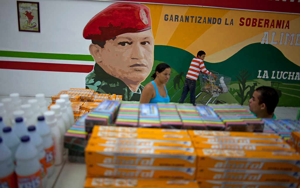 Description of . In this April 8, 2013 photo, a mural of Venezuela's late President Hugo Chavez adorns a supermarket wall as customers shop in Maracay, Venezuela. Outside Venezuela's capital, power outages, food shortages and unfinished projects abound; important factors heading into Sunday's election to replace Chavez, who died last month after a long battle with cancer. Maduro, Chavez's hand-picked successor, is favored to win, largely on the strength of Chavez's generous anti-poverty programs. But recent polls show that support for Maduro may be eroding. (AP Photo/Ramon Espinosa)