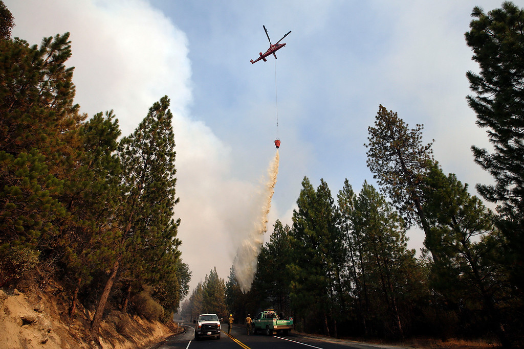 Description of . A helicopter drops water over a hot spot while battling the Rim Fire near Yosemite National Park, Calif., on Sunday, Aug. 25, 2013.  (AP Photo/Jae C. Hong)