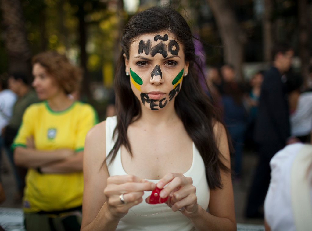 Description of . Marcella Santiago whose face is painted with a message in Portuguese;
