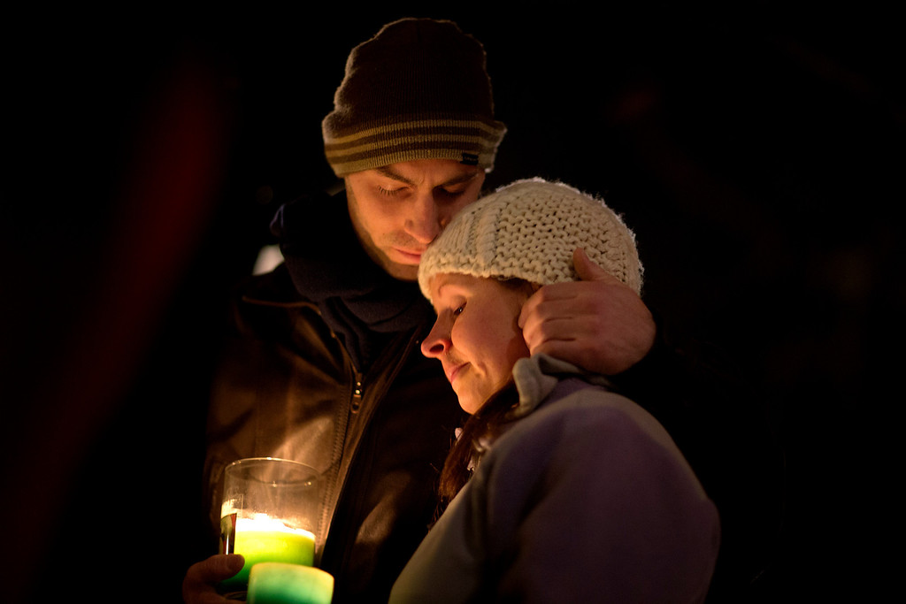 Description of . Brian Tenenhaus, left, comforts Lauren Foster, during a candlelight vigil outside the Edmond Town Hall, Saturday, Dec. 15, 2012, in Newtown, Conn.  A gunman walked into Sandy Hook Elementary School in Newtown Friday and opened fire, killing 26 people, including 20 children. (AP Photo/David Goldman)