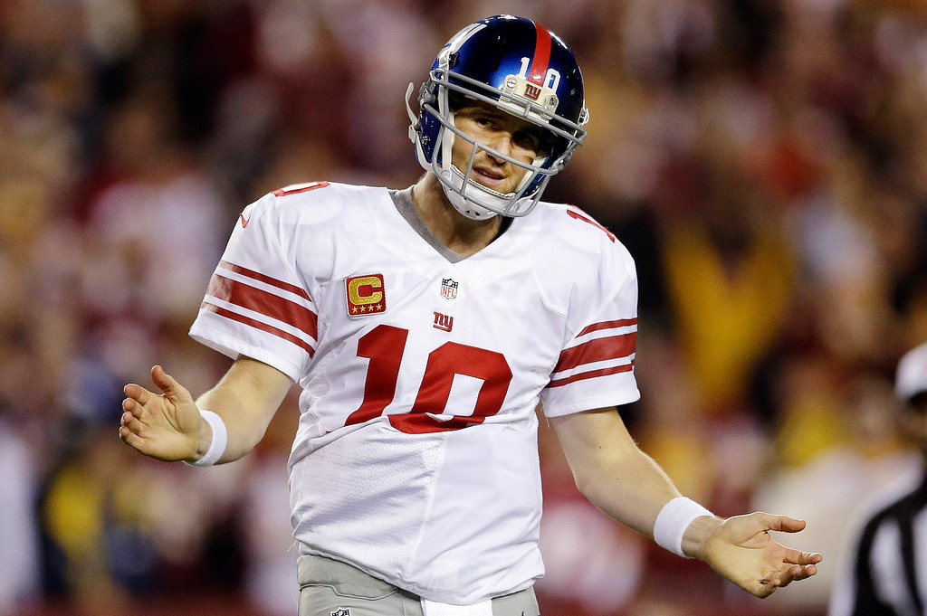 Description of . New York Giants quarterback Eli Manning reacts to a play during the second half of an NFL football game against the Washington Redskins in Landover, Md., Monday, Dec. 3, 2012. (AP Photo/Patrick Semansky)
