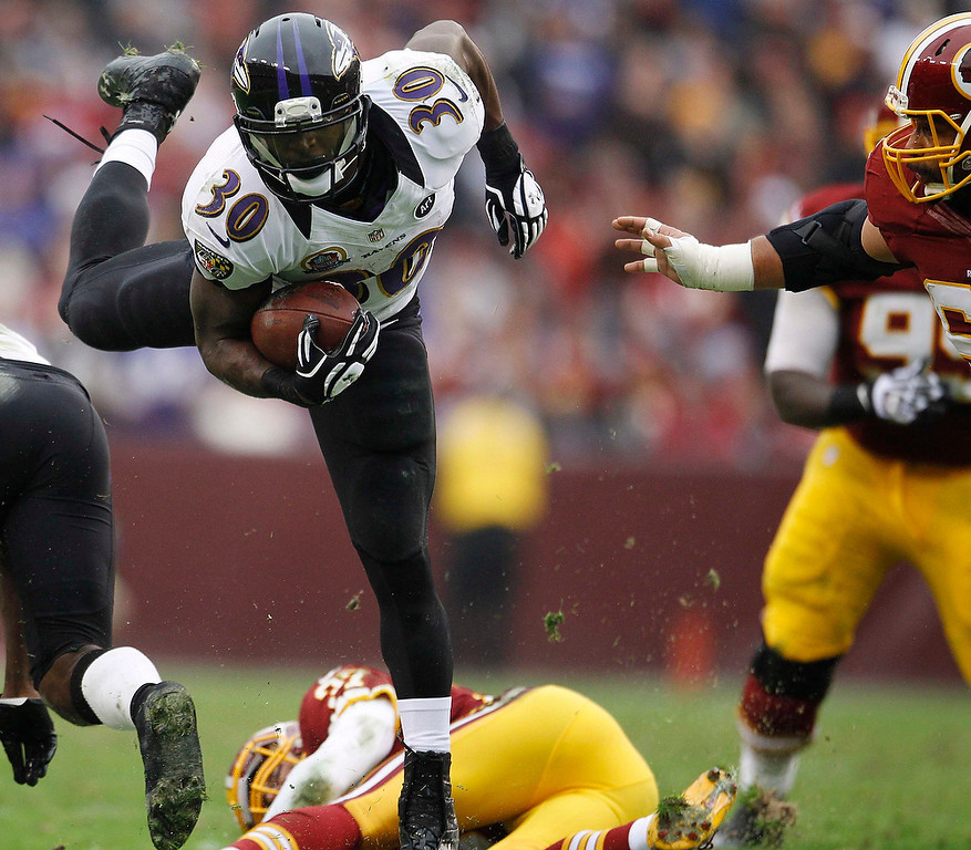 Description of . Baltimore Ravens running back Bernard Pierce (L) leaps through the Washington Redskins defense in the first half of their NFL football game in Landover, Maryland December 9, 2012. REUTERS/Gary Cameron (UNITED STATES - Tags: SPORT FOOTBALL)