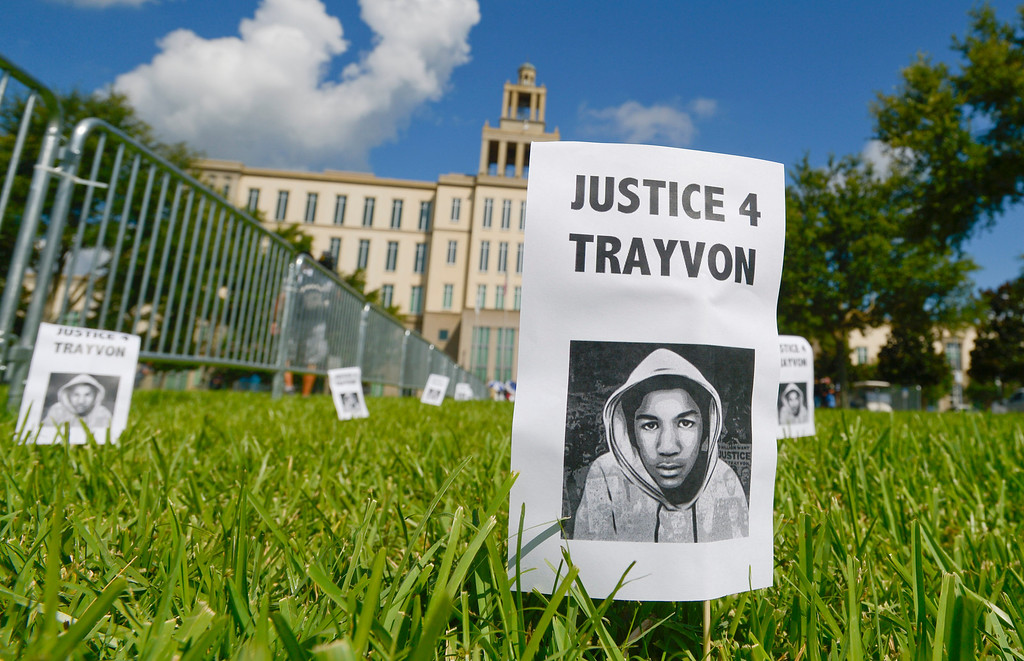 Description of . Signs with a photo of Trayvon Martin are displayed in front of the Seminole County Courthouse during jury deliberations in the George Zimmerman trial, Saturday, July 13, 2013, in Sanford, Fla. Zimmerman has been charged in the 2012 shooting death of Trayvon Martin. (AP Photo/Phelan M. Ebenhack)