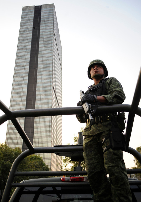 Description of . A soldier stands guard near the headquarters of state oil giant Pemex in Mexico City January 31, 2013. A powerful explosion rocked the Mexico City headquarters of state oil giant Pemex on Thursday, killing at least 14 people and injuring 100 others.   REUTERS/Alejandro Dias