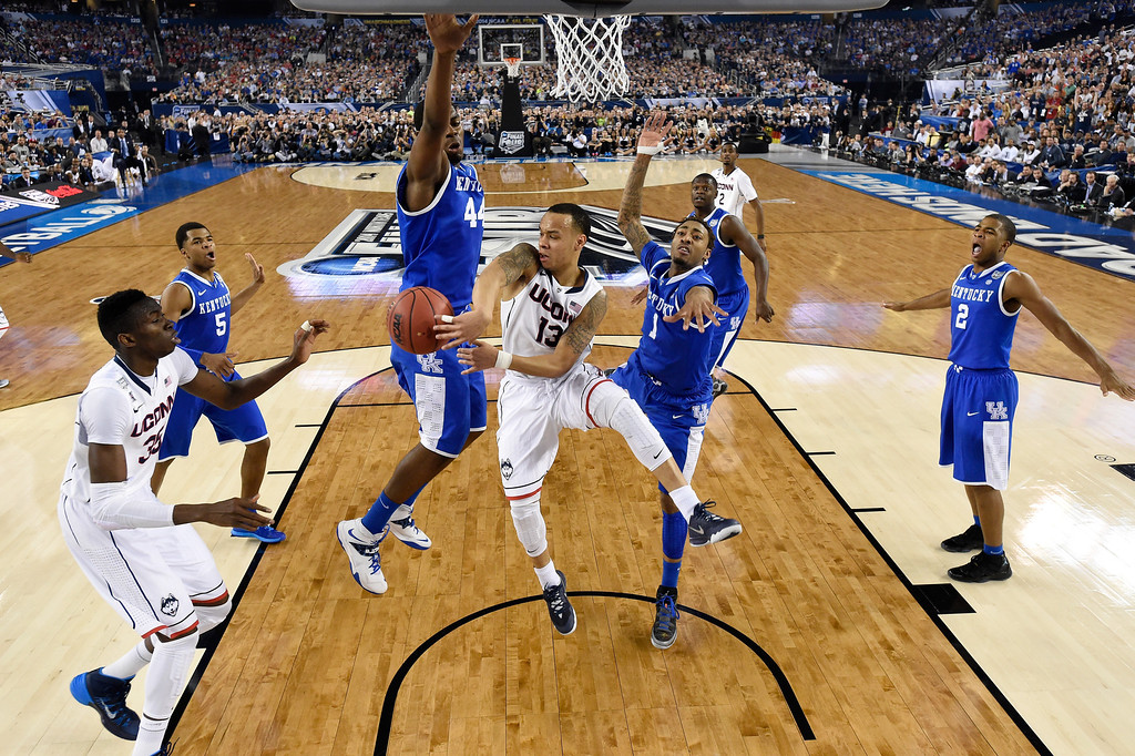 Description of . ARLINGTON, TX - APRIL 07:  Shabazz Napier #13 of the Connecticut Huskies passes as James Young #1 of the Kentucky Wildcats defends during the NCAA Men\'s Final Four Championship at AT&T Stadium on April 7, 2014 in Arlington, Texas. (Photo by Chris Steppig-Pool/Getty Images)