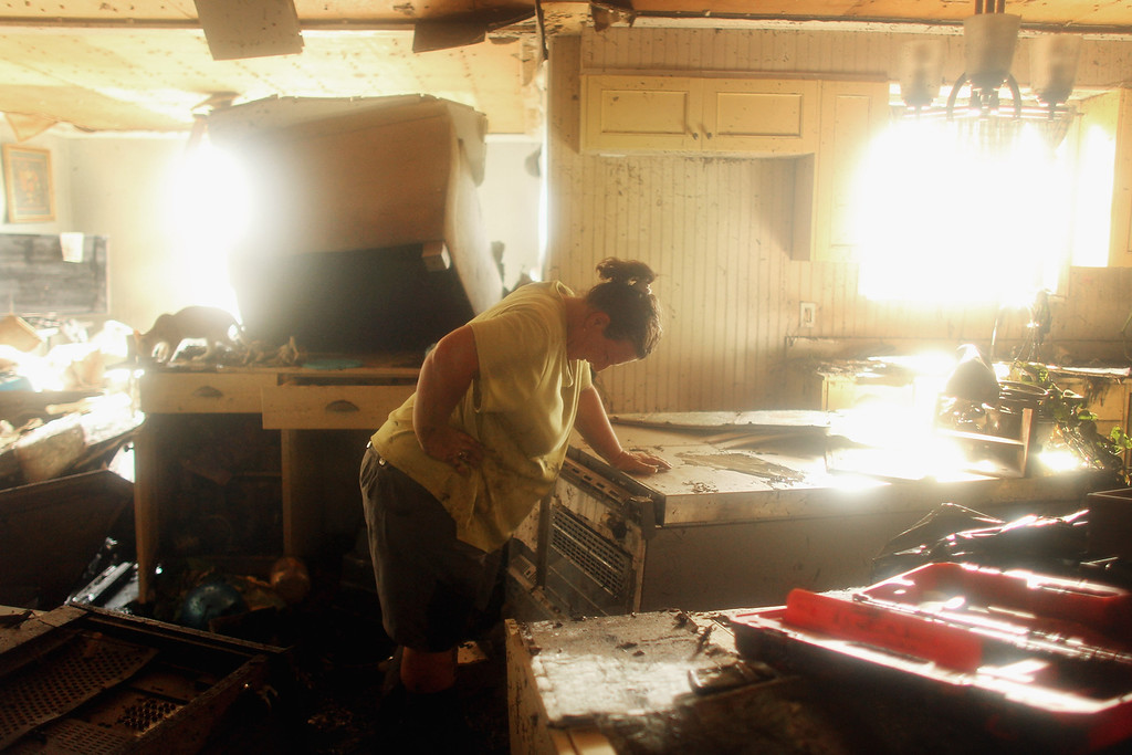 Description of . Melanie Martinez pauses while salvaging items in her flooded home in Plaquemines Parish on September 3, 2012 in Braithwaite, Louisiana. Martinez, along with her husband and mother, was forced to ride out the storm in the home when their car broke down. The house quickly flooded and they were rescued by a neighbor who was able to break into their attic to save them. This is the fifth home Martinez has had destroyed due to hurricanes in Louisiana. Damage totals from the hurricane could top $2 billion and more than 125,000 customers are still without power six days after the storm made landfall.  (Photo by Mario Tama/Getty Images)