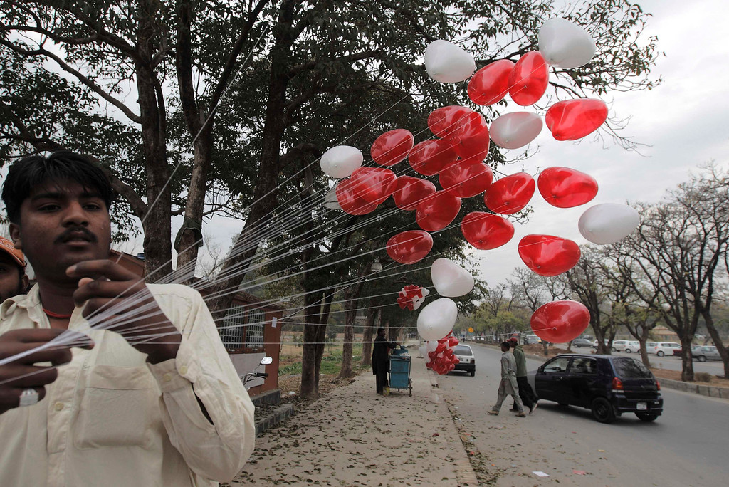 Description of . A street seller ties up heart-shaped balloons on Valentine's Day in Islamabad February 14, 2013. REUTERS/Zohra Bensemra