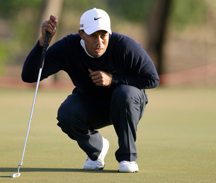 . Tiger Woods from U.S. lines up his ball on the 13th hole during the first round of Abu Dhabi Golf Championship in Abu Dhabi, United Arab Emirates, Thursday, Jan. 17, 2013. (AP Photo/Kamran Jebreili)