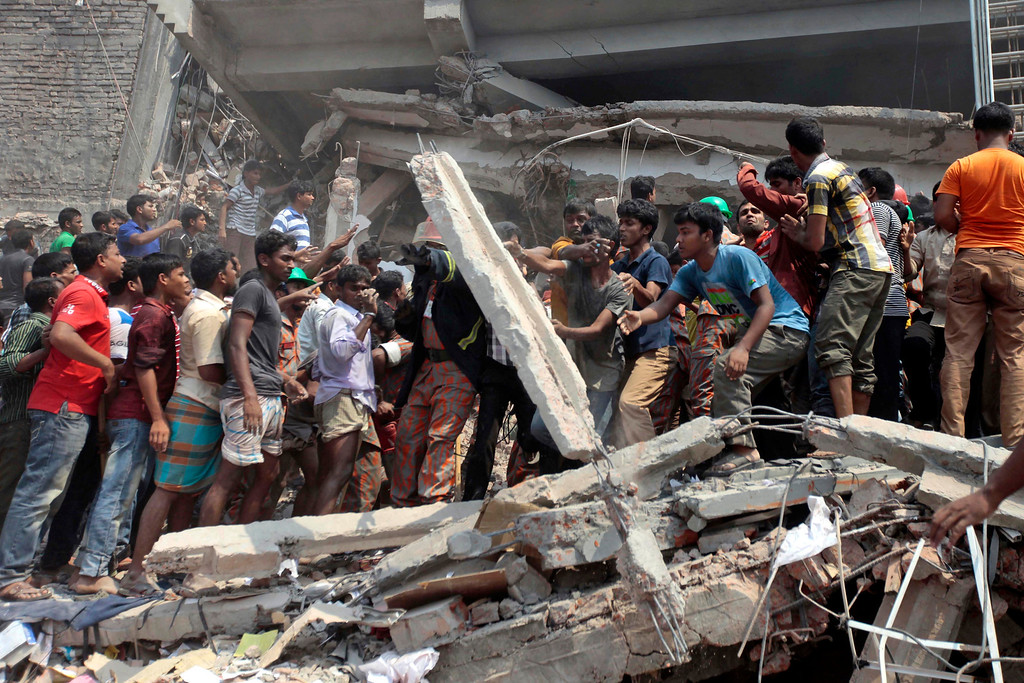 Description of . Rescue workers remove concrete slabs as they look for survivors after an eight-story building housing several garment factories collapsed in Savar, near Dhaka, Bangladesh, Wednesday, April 24, 2013.(AP Photo/ A.M. Ahad)