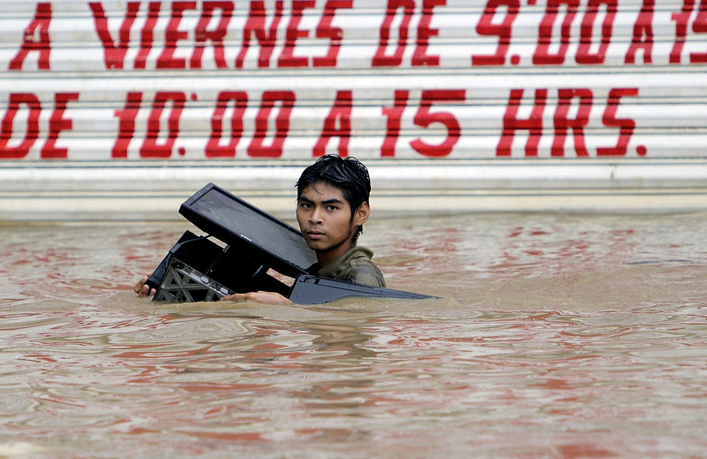 Description of . TOPSHOTS A young man carrying a stolen computer wades through a flooded street in Acapulco, Guerrero state, Mexico, after heavy rains hit the area on September 16, 2013. Hurricane Ingrid weakened to tropical storm strength as it made landfall on the northeastern coast in the morning while the Pacific coast was reeling from the remnants of Tropical Storm Manuel, which dissipated after striking on the eve. Thousands of people were evacuated on both sides of the country as the two storms set off landslides and floods that damaged bridges, roads and homes.   STR/AFP/Getty Images