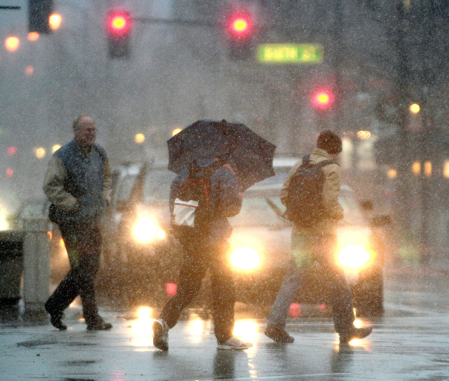 Description of . Pedestrians hurry through the intersection of Wright and Green Streets in Champaign, Ill., as a winter storm begins to blanket the area, Thursday, Dec. 20, 2012. (AP Photo/The News-Gazette, John Dixon)