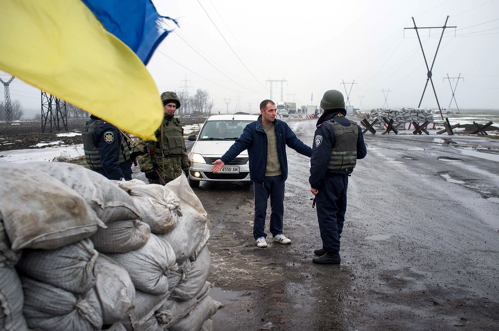 Description of . Ukrainian forces servicemen check passengers of a car at a checkpoint in the eastern Ukrainian city of Kurakhove, near Donetsk on January 21, 2015. Heavy fighting raged between Ukrainian forces and pro-Russian rebels in the country's war-torn east Wednesday, killing at least five more civilians ahead of high-stakes peace talks in Berlin. Oleksandr Stashevskiy/AFP/Getty Images