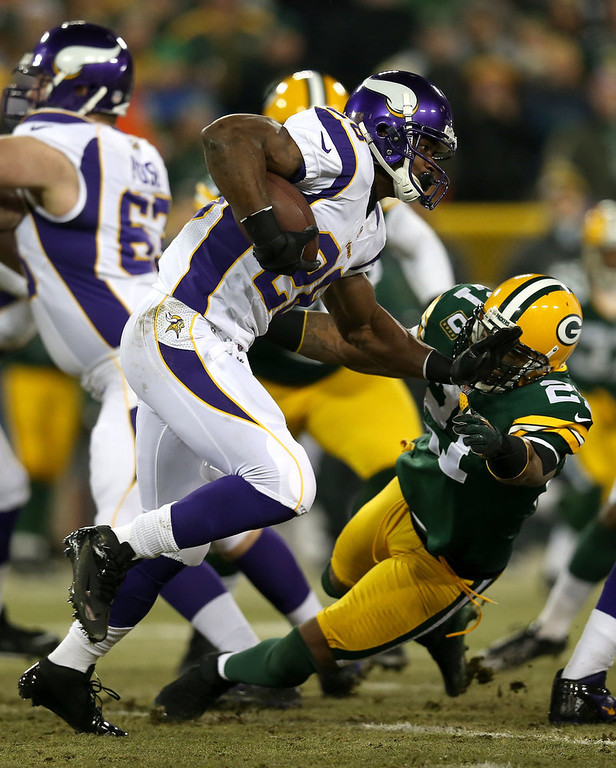 Description of . Running back Adrian Peterson #28 of the Minnesota Vikings runs the ball against safety Charles Woodson #21 of the Green Bay Packers in the first quarter during the NFC Wild Card Playoff game at Lambeau Field on January 5, 2013 in Green Bay, Wisconsin.  (Photo by Jonathan Daniel/Getty Images)