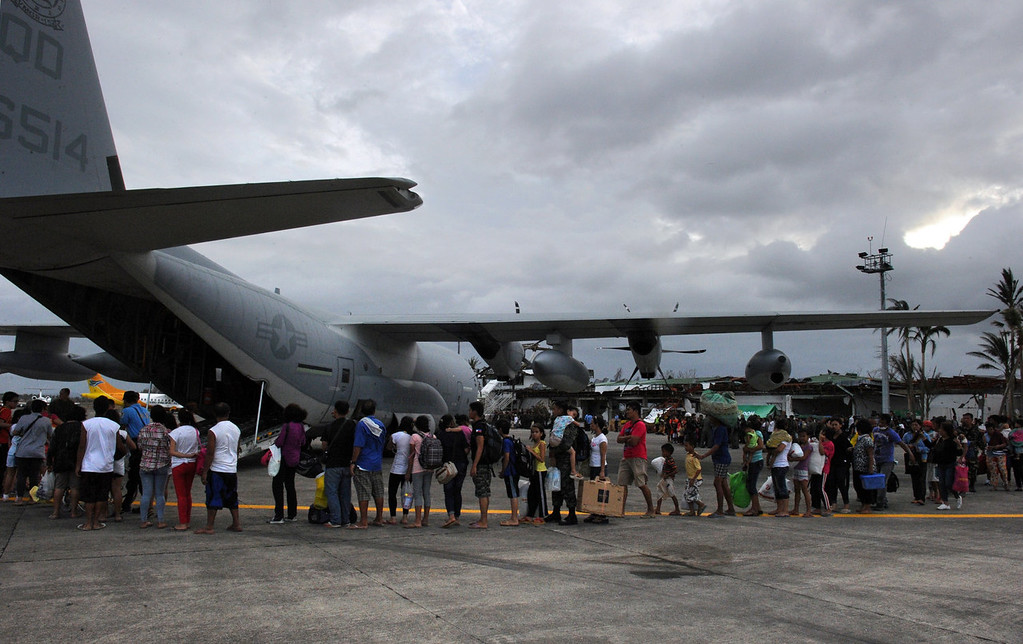 Description of . Survivors of Super Typhoon Haiyan queue up to board a US military C-130 plane for Manila after the plane arrived carrying relief supplies at Tacloban airport in the central Philippines on November 11, 2013, after Super Typhoon Haiyan devastated the city on November 8.  US military planes on November 11 joined a frantic effort to rescue famished survivors of the monster typhoon that may have killed 10,000 people in the Philippines, as local security forces struggled to contain looting.    TED ALJIBE/AFP/Getty Images