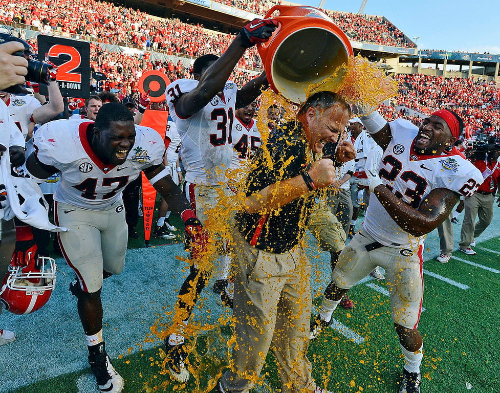 Description of . Georgia head coach Mark Richt, center, is doused by defensive end Ray Drew (47), flanker Chris Conley (31) and free safety Marc Deas (23) after their 45-31 win over Nebraska in the Capital One Bowl NCAA college football game, Tuesday, Jan. 1, 2013, in Orlando, Fla. (AP Photo/Atlanta Journal-Constitution, Brant Sanderlin)